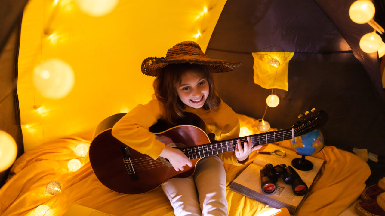 Little girl playing acoustic guitar under the tent in a living room.