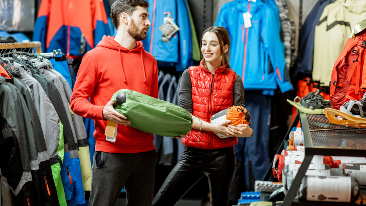 Man and woman choosing traveling equipment in the shop
